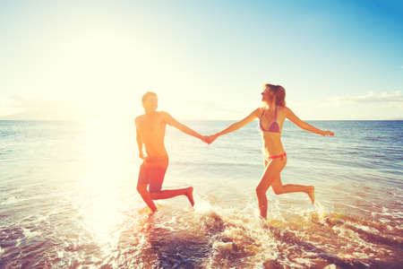 young lovers: Happy Couple Playing and Running on the Beach at Sunset Stock Photo