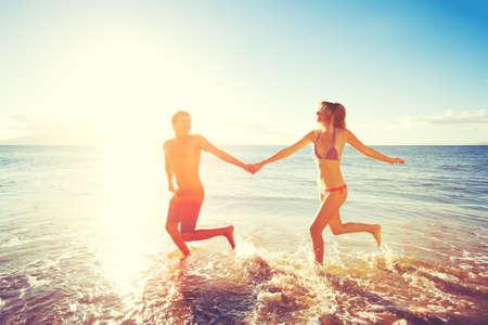amantes: Juego de Pareja Feliz y ejecuta en la playa al atardecer Foto de archivo