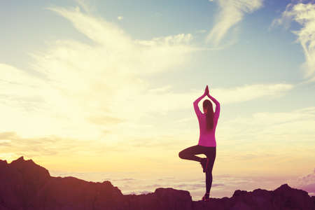 Young Woman Practicing Yoga in the Mountains at Sunset, Healthy Active Lifestyle Stockfoto