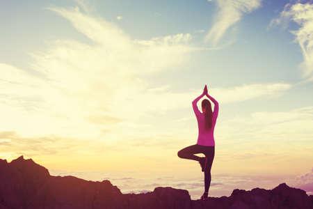 Praticando da mulher nova Ioga nas montanhas ao pôr do sol, estilo de vida activo e saudável