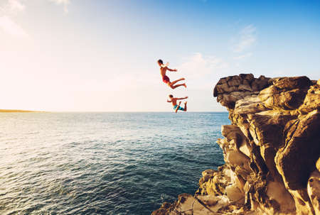Vrienden cliff jumping in de oceaan bij zonsondergang, Outdoor Adventure Lifestyle