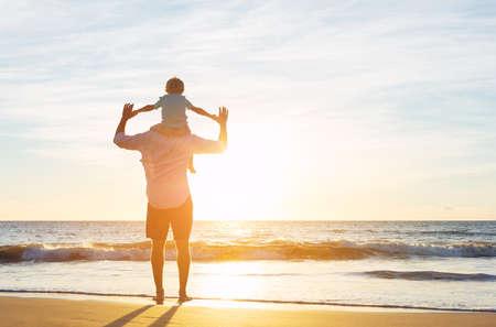 sol radiante: Feliz padre e hijo se divierten juegan en la playa al atardecer. Paternidad Familia Concepto Foto de archivo