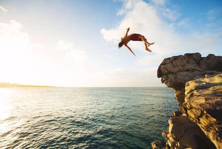 崖日没、屋外の冒険ライフ スタイルで海に飛び込む