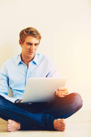 trabajando en casa: Hombre joven Usar el portátil Trabaje desde su casa Foto de archivo