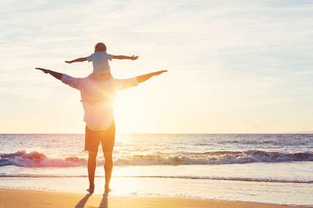Счастливый отец и сын весело играя на пляже на закате. Отцовство Семья Концепция