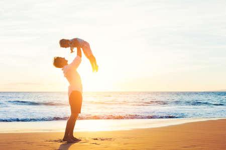 dia soleado: Feliz alegre Padre e hijo que se divierten jugando en la playa en la puesta del sol. Concepto de familia paternidad Foto de archivo