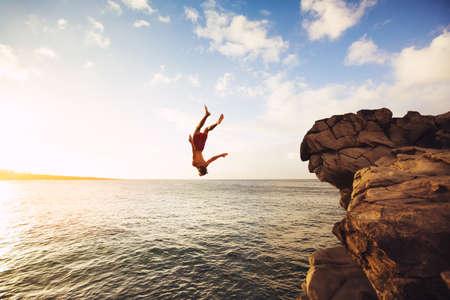 jumping: Acantilado de salto en el océano en la puesta del sol, aventura al aire libre Estilo de vida