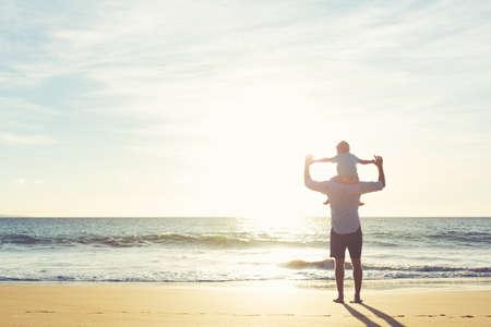 dia soleado: Feliz padre e hijo se divierten juegan en la playa al atardecer. Paternidad Familia Concepto Foto de archivo