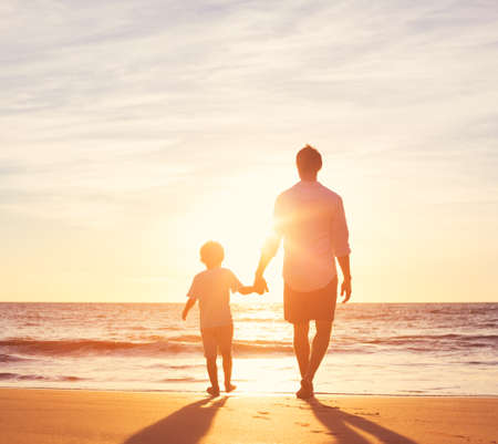 Padre e figlio di camminare insieme sulla spiaggia al tramonto. Paternità concetto di famiglia Archivio Fotografico