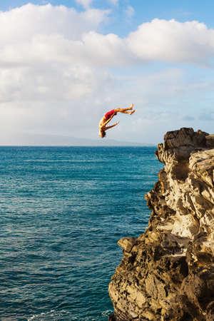 persona saltando: Acantilado de salto en el océano en la puesta del sol, la diversión del verano Estilo de vida