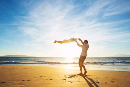 Happy Joyful Father and Son Playing on the Beach at Sunset. Fatherhood Family Concept Stockfoto