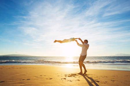 verano: Padre feliz alegre e hijo que juegan en la playa en la puesta del sol. Paternidad Familia Concepto