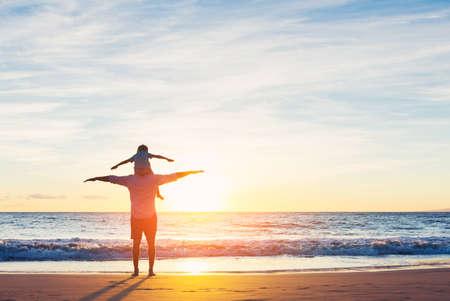 Pai feliz e filho que têm o divertimento jogar na praia no por do sol. Paternidade conceito de família