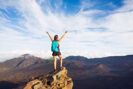 Young happy woman hiker with backpack standing on mountain peak with open arms Banco de Imagens