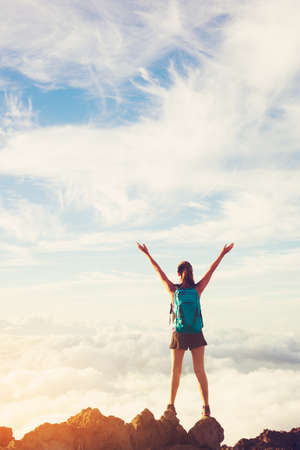 top mountain: Happy Young Woman Hiker With Open Arms Raised at Sunset on Mountain Peak Stock Photo
