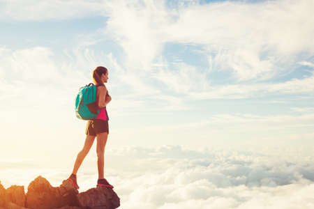 Woman Hiking in the Mountains Above the Clouds at Sunset, Adventure Outdoor Active Lifestyle Archivio Fotografico