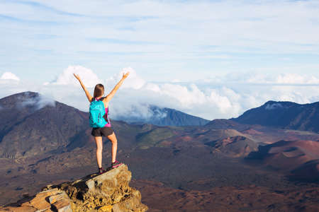 Young happy woman hiker with backpack standing on mountain peak with open arms Imagens - 48837223