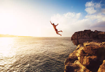hombre cayendo: Acantilado de salto en el océano en la puesta del sol, la diversión del verano Estilo de vida