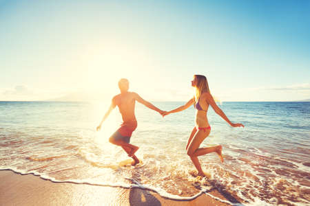 romantic couple: Happy Couple Playing and Running on the Beach at Sunset Stock Photo
