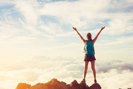 sunrise mountain: Happy Young Woman Hiker With Open Arms Raised at Sunset on Mountain Peak Stock Photo