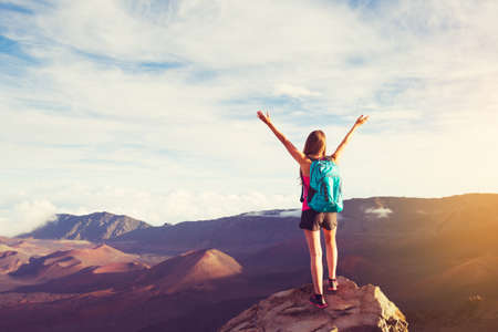 cheer: Happy Young Woman Hiker With Open Arms Raised at Sunset on Mountain Peak Stock Photo