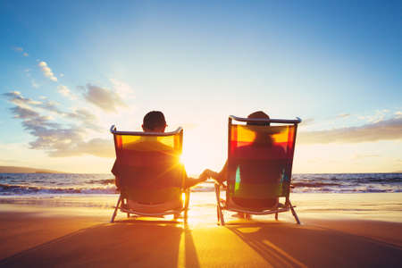 vacation: Retirement Vacation Concept, Happy Mature Retired Couple Enjoying Beautiful Sunset at the Beach