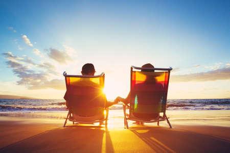 Ruhestandsferien-Konzept, glückliches reifes pensioniertes Paar, das schönen Sonnenuntergang am Strand genießt Standard-Bild