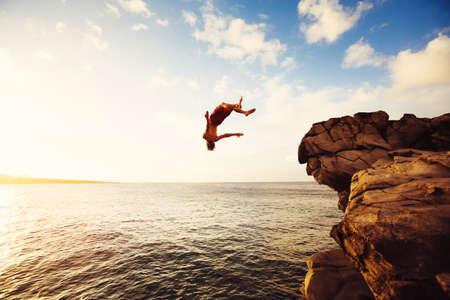 hombre cayendo: Acantilado de salto en el océano en la puesta del sol, aventura al aire libre Estilo de vida