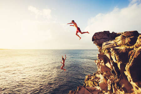 brincando: Amigos acantilado saltando en el océano en la puesta del sol, aventura al aire libre Estilo de vida