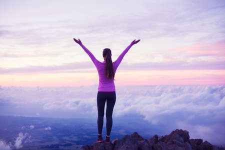 Happy Young Woman Hiker With Open Arms Raised at Sunset on Mountain Peak Banque d'images