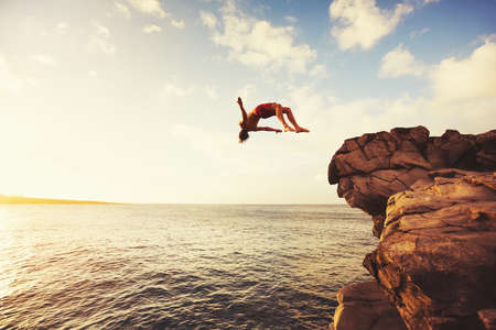 saltando: Acantilado de salto en el oc�ano en la puesta del sol, la diversi�n del verano Estilo de vida