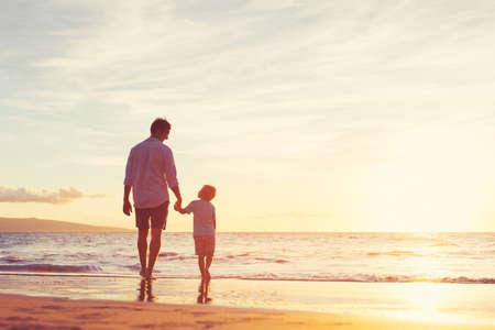 Padre e hijo caminando juntos en la playa al atardecer. Concepto de familia paternidad Foto de archivo - 48958003