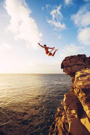 saltando: Acantilado de salto en el oc�ano en la puesta del sol, aventura al aire libre Estilo de vida