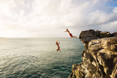 adventure holiday: Friends Cliff Jumping into the Ocean at Sunset, Outdoor Adventure Lifestyle