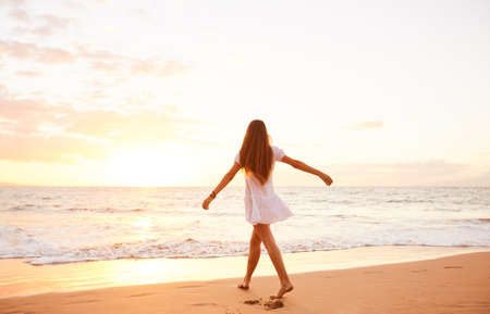 woman sunset: Happy carefree woman dancing at sunset on the beach. Happy free lifestyle concept.