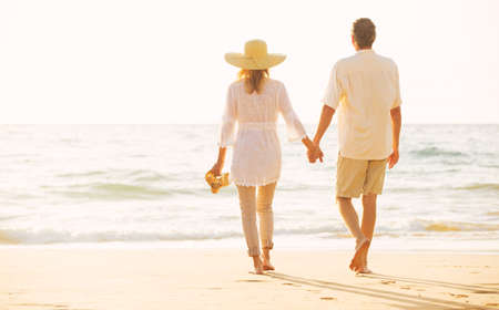 Happy Romantic Middle Aged Couple Enjoying Beautiful Sunset Walk on the Beach Holding Hands Stockfoto