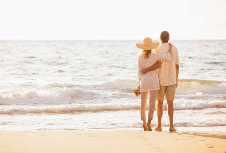 ロマンチックな中年カップルのビーチに沈む夕日を楽しんで満足しています。旅行休暇退職ライフ スタイル コンセプト。 写真素材