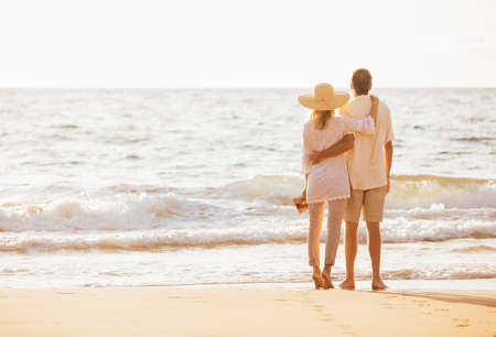 retirement: Happy Romantic Middle Aged Couple Enjoying Beautiful Sunset on the Beach. Travel Vacation Retirement Lifestyle Concept. Stock Photo