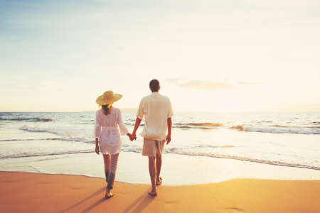 Happy Romantic Middle Aged Couple Enjoying Beautiful Sunset on the Beach. Travel Vacation Retirement Lifestyle Concept. Archivio Fotografico