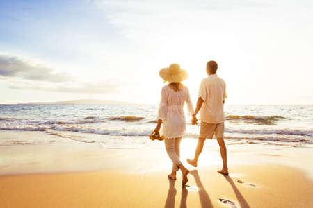 vacation: Happy Romantic Middle Aged Couple Enjoying Beautiful Sunset Walk on the Beach. Travel Vacation Retirement Lifestyle Concept
