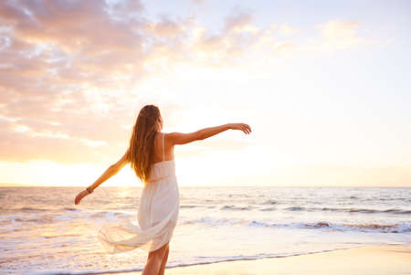 nature beauty: Happy carefree woman dancing at sunset on the beach. Happy free lifestyle concept.
