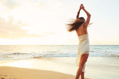 Happy carefree woman dancing at sunset on the beach. Happy free lifestyle concept. Reklamní fotografie - 49495458