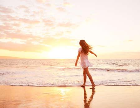 carefree: Happy Carefree Woman Enjoying Beautiful Sunset on the Beach Stock Photo