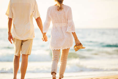 manos sosteniendo: Happy Romantic Middle Aged Couple Enjoying Beautiful Sunset Walk on the Beach Holding Hands Foto de archivo