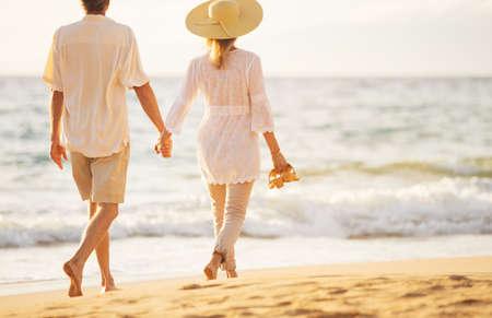 Happy Romantic Middle Aged Couple Enjoying Beautiful Sunset Walk on the Beach Holding Hands Standard-Bild