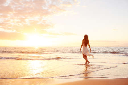 Happy Carefree Woman Enjoying Beautiful Sunset on the Beach Stockfoto