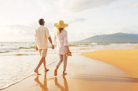 Happy Romantic Middle Aged Couple Enjoying Beautiful Sunset Walk on the Beach. Travel Vacation Retirement Lifestyle Concept Reklamní fotografie - 49643664