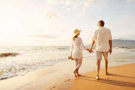 person walking: Happy Romantic Middle Aged Couple Enjoying Beautiful Sunset Walk on the Beach. Travel Vacation Retirement Lifestyle Concept