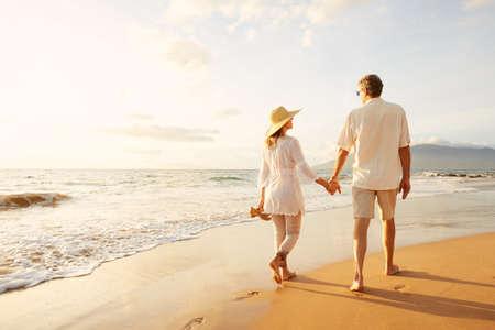 caminando: Romántica feliz pareja de mediana edad Disfrutando del sol hermosa caminata en la playa. Vacaciones Viaje de Retiro Lifestyle Concept