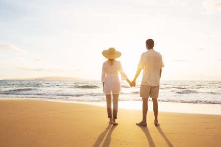 people holding hands: Happy Romantic Middle Aged Couple Enjoying Beautiful Sunset on the Beach. Travel Vacation Retirement Lifestyle Concept. Stock Photo